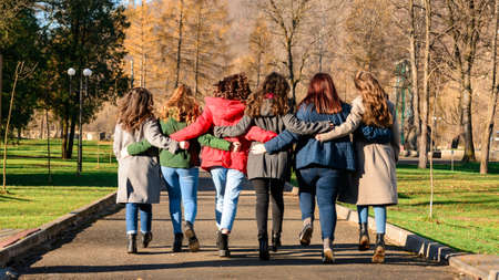 Young group of girls walking in autumn park, autumn clothes and autumn walk. Graduation from high school 2021.