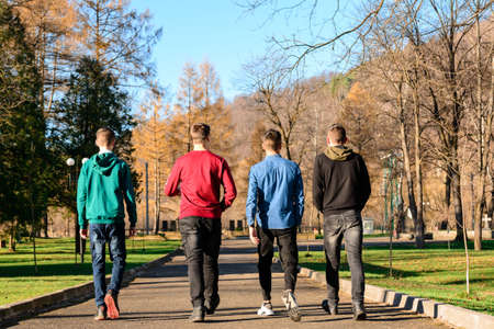 Teen boys walk in autumn park in the city by the river. 2020 版權商用圖片