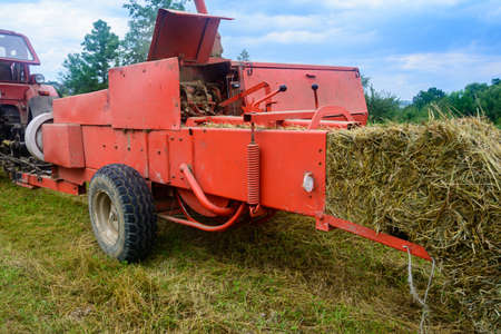 Old bale press, hay harvesting in the village for cattle, press work close up. 2020