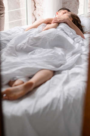 Shooting a young, intimate couple with beautiful bodies, an intimate setting with white sheets. 2020 Banque d'images