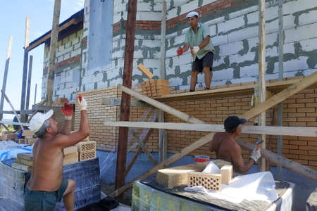 The master throws a brick at his worker for laying the wall. 2019