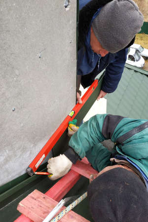 Workers line the chimney with green metal, work without insurance at height, use a level, tape measure and wooden scaffolding.