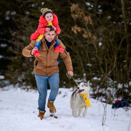 Happy family on a walk in the woods with a husky, jogging with a dog, fun winter games.new