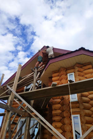 Workers work on top, roof insulation and finishing work on the roof, wooden scaffolding.new