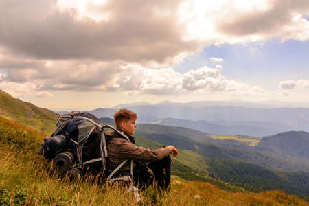 A young tourist sits on a background of mountains with a backpack, relaxing and admiring the views of the Carpathians in Ukraine.2020