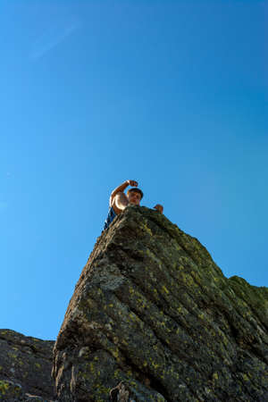 A tourist on top of a large stone block, the top of Smotrych mountain, one of the rocky peaks of the Ukrainian Carpathians. 2020 Фото со стока