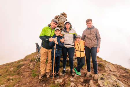 A family of tourists on top of a cloudy mountain in the Carpathians, the mountain of two thousand Gutin Tomnatyk, bold tourists in the mystical white clouds. 2020 Imagens