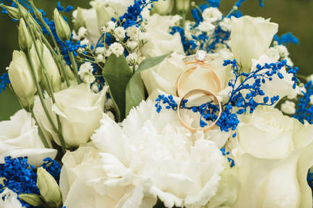 Delicate bouquet for the bride and engagement rings, photo close up. 2020