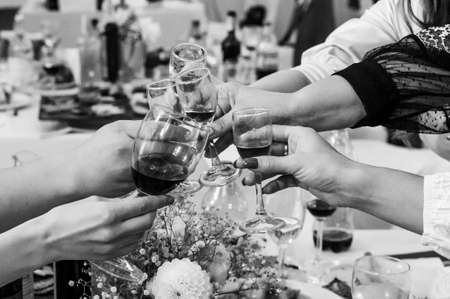 Black and white photo of a party with a speech of toasts. Close-up of female hands with glasses and alcohol with a festive new table.