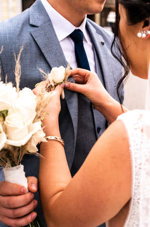 The bride puts a boutonniere on the groom's jacket on their wedding new day.