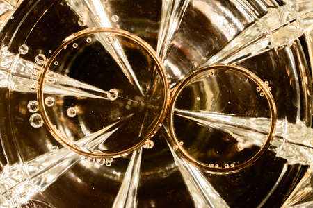 bridal rings on the bottom of a glass of water, bubbles and glitter of light. 2020 Imagens