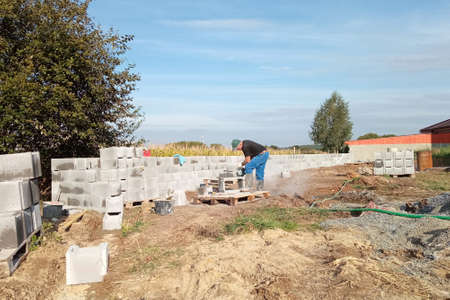 Construction of a fence on a private territory, a worker while performing work. 2020