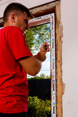 Dolyna, Ukraine July 31, 2020: an employee installs a window frame, installing a plastic window. new