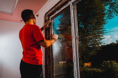 Dolyna, Ukraine July 31, 2020: an employee installs a window in the house, installation of a plastic window, wds windows, energy-saving windows.new
