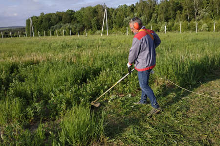 Man mows the grass with a trimmer, tall grass in a meadow, handmade in the garden.new