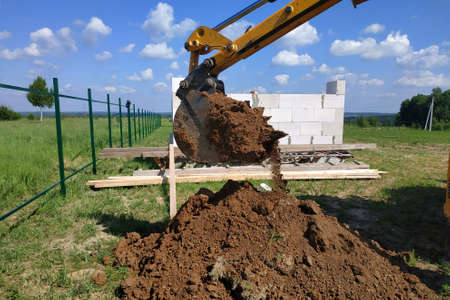 The yellow excavator digs a trench, construction works by means of automobile equipment.new