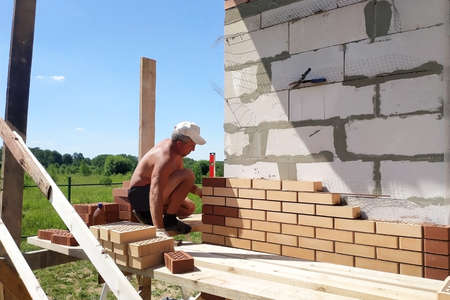The master puts a laying from a front brick, warming of the house outside, construction works in the summer.new Archivio Fotografico