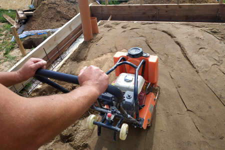 Working with a vibrating machine and equipment, soil compaction with a vibrating plate.new
