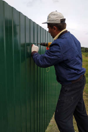 The worker with a screwdriver screws the screws into the fence, installing a metal fence.new Archivio Fotografico