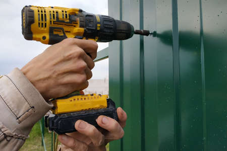 Fastening of a metal sheet to a framework of a fence by means of the screw-driver, screwing of screw-drivers in a fence.new