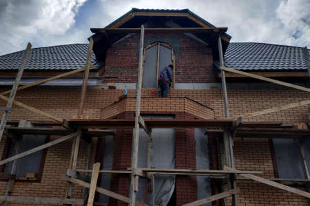 Insulation of the house with facade bricks, construction of a new house and scaffolding near the walls.new