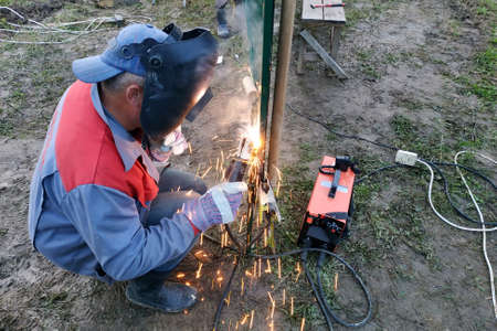 welding of a metal profile to a fence, process of welding close-up, the worker in a protective helmet against sparks.new Archivio Fotografico