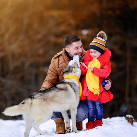 Happy father with daughter and their pet in winter park, walking with dog.new Archivio Fotografico
