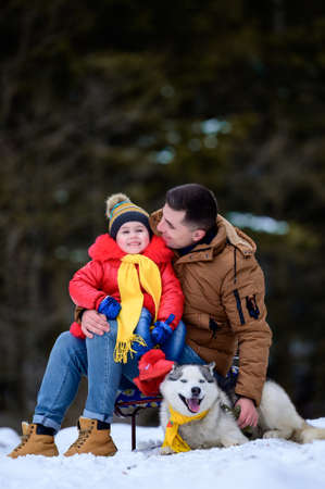A father with a beautiful daughter and a husky dog are walking in the winter forest.
