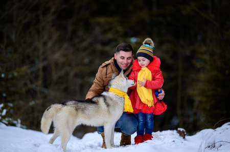 Happy father with daughter and their pet in winter park, walking with dog.