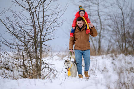 Winter walk, father with daughter and dog in the woods, bright winter clothes.