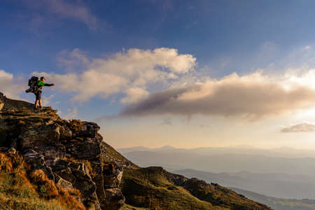 A little boy standing on a large rocky rock admires the landscape of the Carpathians, the top of Mount Pip Ivan Chornohirsky. 2020