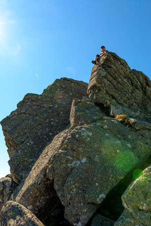 A tourist on top of a large stone block, the top of Smotrych mountain, one of the rocky peaks of the Ukrainian Carpathians. 2020 Banque d'images