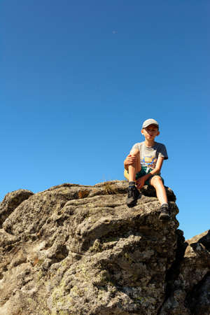 boy sitting on the edge of a large rocky rock, summer hike in the mountains, the top of the mountain. 2020