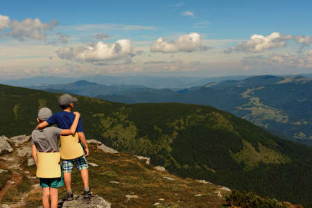 Two small children, brothers boys standing on one rocky peak, a mountain of Carpathian mountains, happy children, children on a hike. 2020