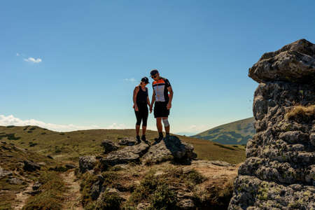 Silhouette of a couple on top of a mountain, tourists on top of a Carpathian mountain, Montenegrin ridge. 2020