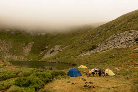 Morning rain and fog near a mountain lake, Carpathian lake Brebeneskul, a tent camp in the fog. 2020 Banque d'images