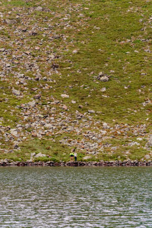 A couple of tourists stand on the edge of a mountain lake, Lake Brebeneskul, the Montenegrin ridge, the Carpathians of Ukraine. 2020
