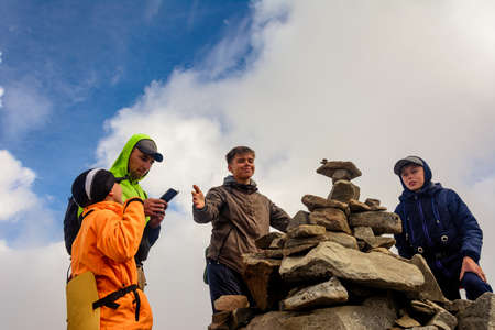 A group of tourists sits on top of the mountain in sportswear, the Montenegrin ridge and the top of Mount Rebra. 2020
