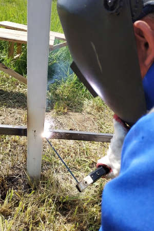 At the construction site, the master welds a metal profile for the fence. 2019 Banque d'images