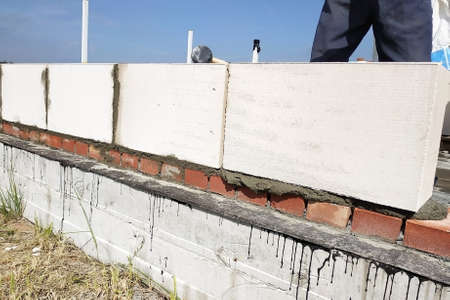 The worker measures the work out wall with a level. 2019