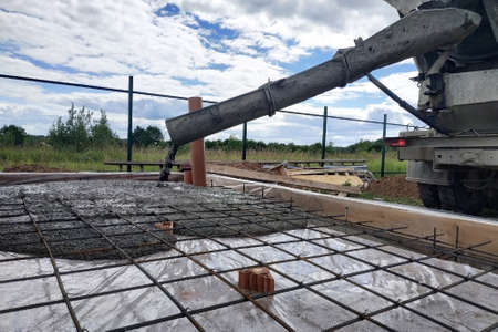 Pouring concrete after placing steel reinforcement to make a screed, the photo shows sewer pipes. 2019