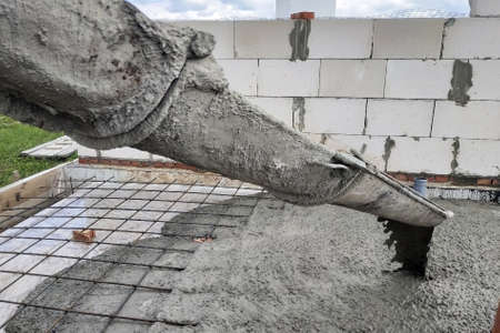 The concrete mixer feeds cement through the gutter to pour the concrete slab, sewer pipes are visible. 2019 Banque d'images