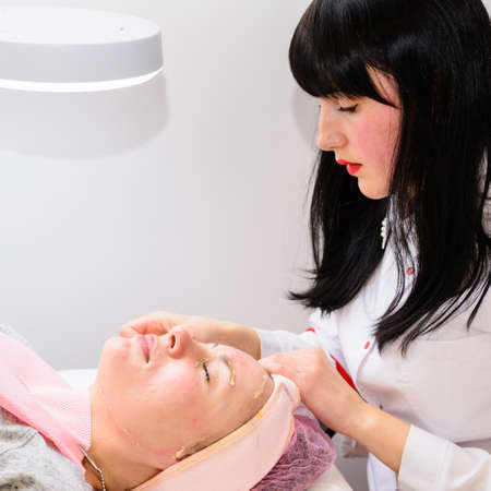 Facial massage at the beautician at the reception, visiting a beauty salon, a sense of relaxation. new
