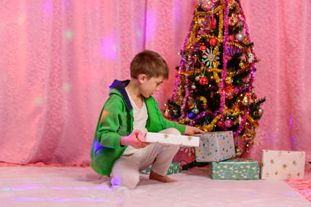 A child near the Christmas tree considers Christmas gifts, a photo shoot at home. new