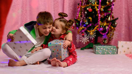 A brother and sister are looking at presents near the Christmas tree on Christmas Eve. new
