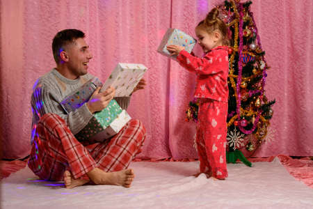 Dad and daughter are considering Christmas presents, a homely atmosphere, a girl and a man in pajamas. new
