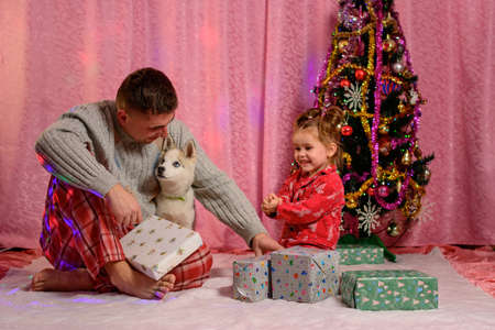 Dad with daughter and husky puppy sitting by the Christmas tree, dad and daughter in pajamas. new