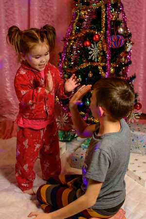 Brother and sister open Christmas presents near the Christmas tree, Christmas Eve event, happy children. new