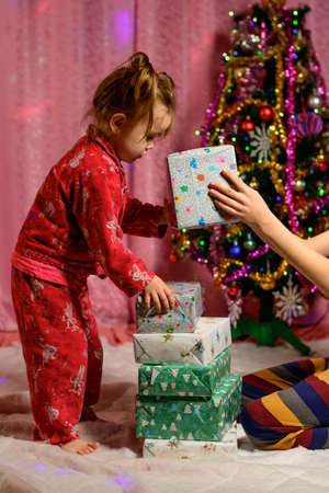 Girl in red pajamas holding Christmas presents, Christmas celebrations and happy children's moments. new