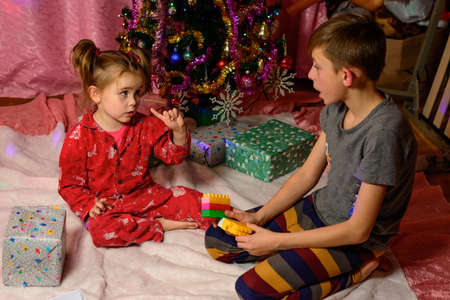 Brother and sister open presents near the Christmas tree, Christmas Eve event, happy children. new Stock fotó